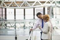 Business people using digital tablet in atrium - HEROF26727