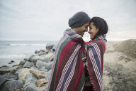Affectionate couple wrapped blanket face to face beach - HEROF26766