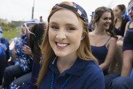 Close up portrait smiling fan in blue bleachers - HEROF26811