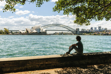 Australia, New South Wales, Sydney, man looking towards the bridge and the Sydney opera house - KIJF02347