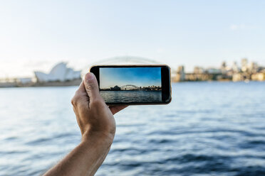 Australia, New South Wales, Sydney, close-up hand of man taking a picture with mobile phone to Sydney - KIJF02356