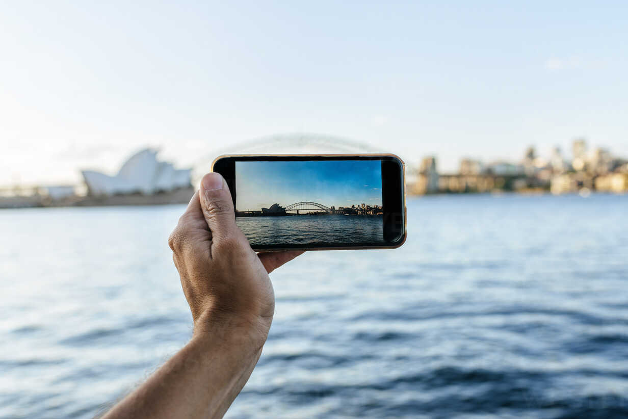 Australia, New South Wales, Sydney, close-up hand of man taking a picture with mobile phone to Sydney - KIJF02356 - Kiko Jimenez/Westend61