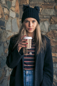 Portrait of young woman with coffee to go wearing coat and woolly hat - ACPF00472