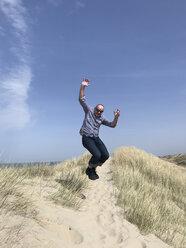 Belgium, Flanders, North Sea Coast, man jumping in dunes - GWF05904