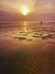 Belgium, Flanders, North Sea Coast, man relaxing, doing excercise and enjoying freedom while watching sunset and ocean waves, listening to ocean sounds - GWF05907