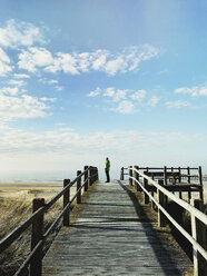 Belgium, Flanders, North Sea, Coast, man standing on boardwalk in sand dunes, relaxing, watching ocean and listening to ocean sounds in warm spring sunshine - GWF05913