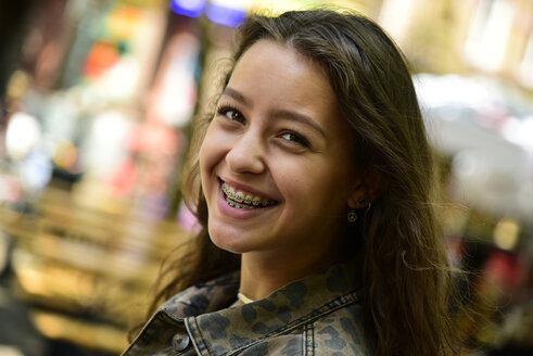 Portrait of laughing teenage girl wearing braces - MIZF00795