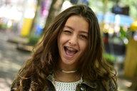 Portrait of winking teenage girl wearing braces - MIZF00798