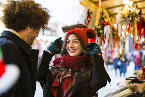 Happy young couple at Christmas market with woman trying on wooly hat - MGIF00301