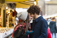 Happy affectionate young couple at Christmas market - MGIF00304