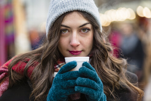 Portrait of beautiful young woman holding hot drink at Christmas market - MGIF00307