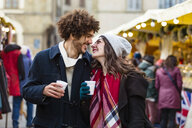 Happy affectionate young couple with hot drinks at Christmas market - MGIF00310