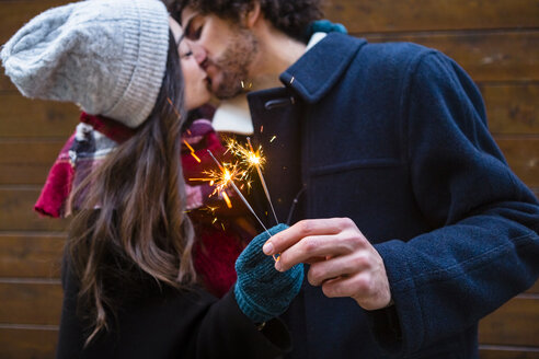 Young couple in winterwear kissing and holding sparklers in front of wooden wall - MGIF00319