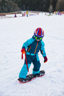 Italy, Trentino-Alto Adige, boy riding on small snowboard on piste - MGIF00327