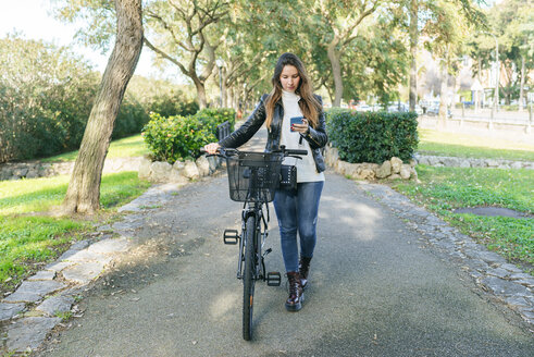 Young woman with bicycle in park using cell phone - KIJF02363