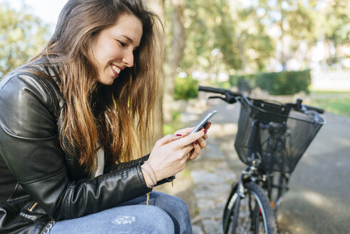 Young woman with bicycle sitting in park using cell phone - KIJF02369