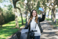 Smiling young woman with bicycle in park taking a selfie - KIJF02375