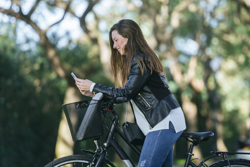 Smiling young woman with bicycle in park using cell phone - KIJF02381