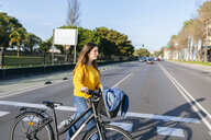 Young woman with bicycle crossing the street - KIJF02390