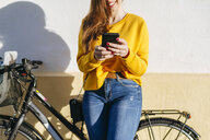 Close-up of young woman with bicycle using cell phone at a wall - KIJF02393