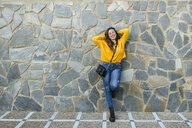 Portrait of happy young woman leaning against a stone wall - KIJF02396