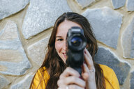 Portrait of young woman with vintage camera at a stone wall - KIJF02399