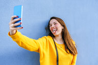 Happy young woman taking a selfie at a wall sticking out tongue - KIJF02402