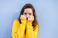 Portrait of happy young woman with yellow pullover at blue wall - KIJF02405