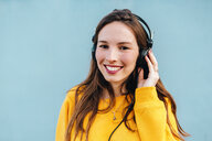 Portrait of smiling young woman listening to music with headphones - KIJF02408