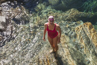 Switzerland, Ticino, Verzasca Valley, portrait of happy woman in swimsuit standing in Verszasca river - GWF05956