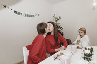 Same sex family celebrating christmas at home, women kissing - KMKF00764