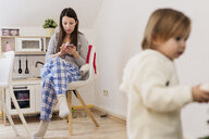 Woman sitting in kitchen using smartphone while little daughter standing in the foreground - KMKF00770
