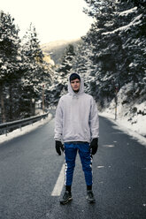 Young man standing on a snowy road with trees in the background - ACPF00481