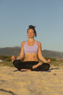 Woman meditating on the beach in the evening - KBF00535