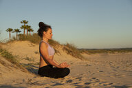 Woman meditating on the beach in the evening - KBF00538