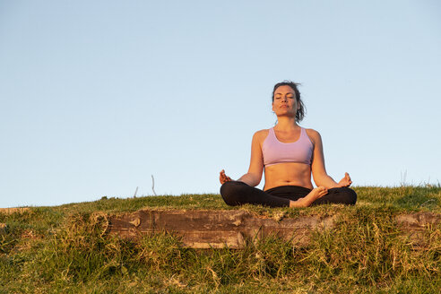 Woman meditating on a meadow in the evening - KBF00541