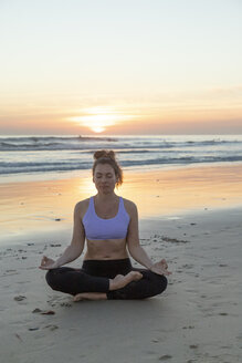 Woman meditating on the beach in the evening - KBF00544