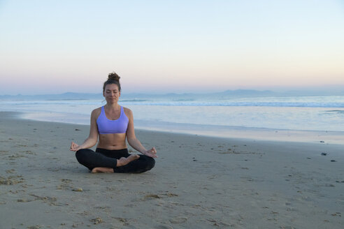 Woman meditating on the beach in the evening - KBF00547