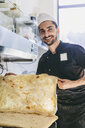 Portrait of smiling chef holding pizza bread in commercial kitchen at pizzeria - CAVF62347