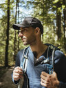 Male hiker with backpack looking away while standing in forest - CAVF62365