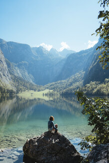 Female tourist looking at lake while sitting on rock against mountains during sunny day - CAVF62374