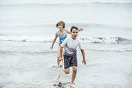 Playful siblings running in sea - CAVF62395