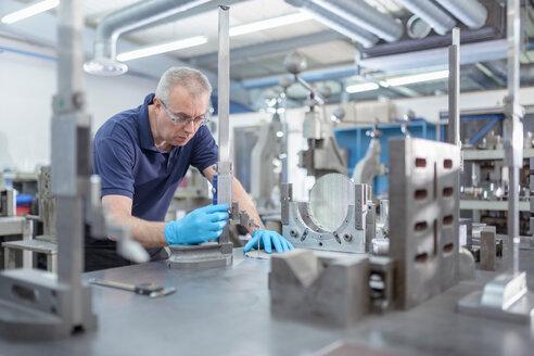 Engineer measuring part in engineering factory - CUF49513
