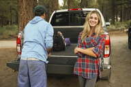 Portrait of smiling woman standing with boyfriend by pick-up truck in forest - CAVF62447