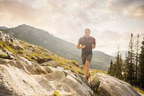 Confident male hiker running on mountain against cloudy sky - CAVF62519