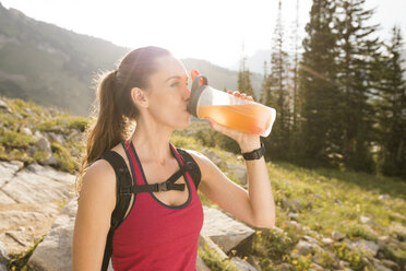 Confident female hiker drinking juice while standing on mountain against sky during sunny day - CAVF62522