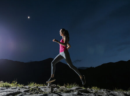 Low angle view of confident female hiker running on rocks against blue sky at night - CAVF62528