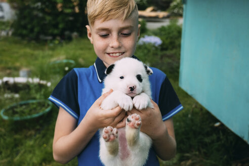 Smiling boy carrying cute puppy while standing in yard - CAVF62591