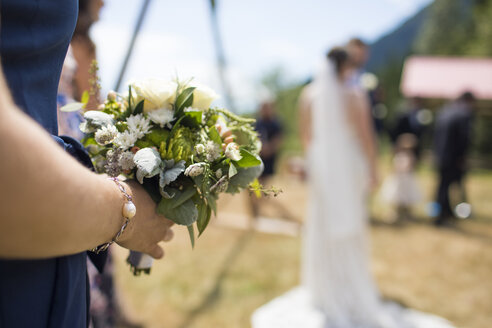 Midsection of bridesmaid holding bouquet while standing against couple in wedding ceremony - CAVF62600