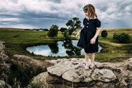 Cute girl looking away while standing on rock against cloudy sky - CAVF62603